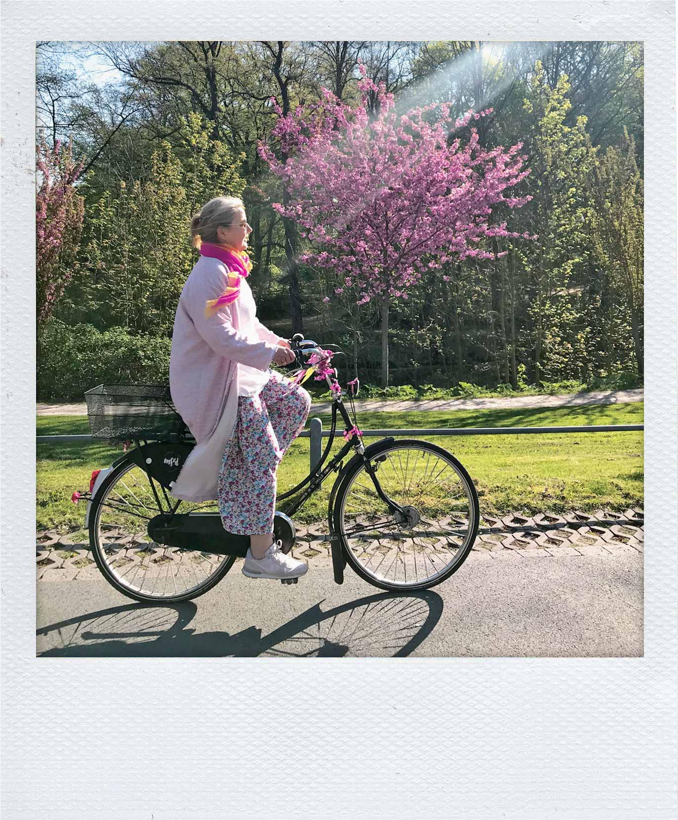 Britta radelt auf ihrem Hollandrad. Im Hintergrund sieht man frühlingshafte Kirschblüten.