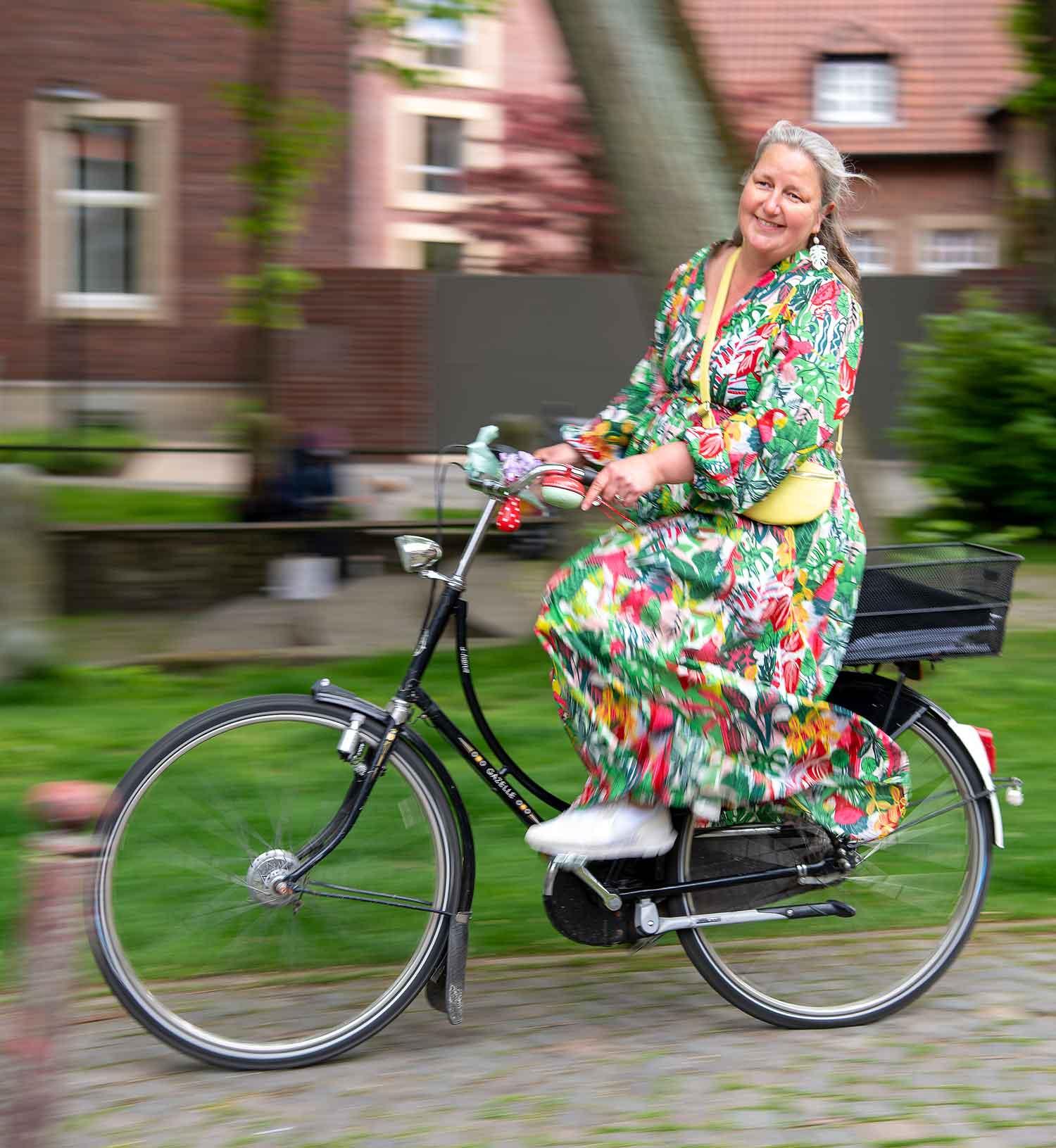 Britta Heithoff im blumigen Kleid auf dem Fahrrad